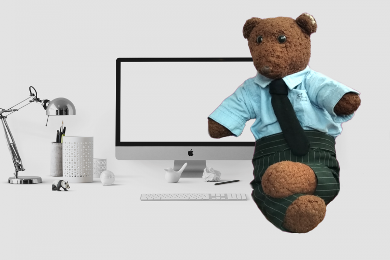 Background image of Bearsac in business attire with computer